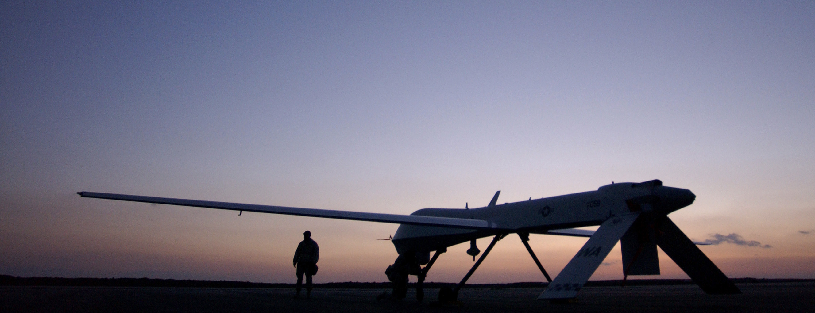 MQ-1 Predator - MQ-1 Predator against the sunset (sunrise?) with a man standing next to it.