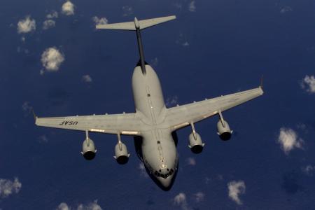 C-17 Globemaster III - C-17 Globemaster III flies over a blue ocean.