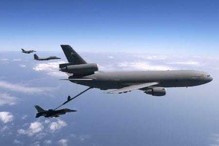 KC-10 Extender - KC-10 Extender refueling a jet with two other jets in the background.